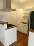 white kitchen with butcher block counter tops and stainless steal appliances